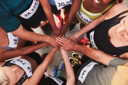 Foto de High angle portrait of a sports team standing in a circle with their hands stacked. Team of runners with hands together after competition. - Imagen libre de derechos