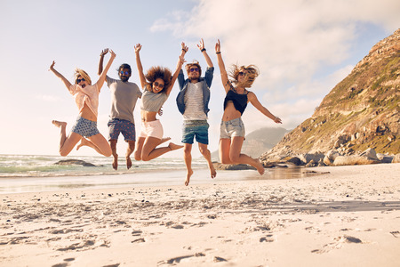 Foto de Group of friends together on the beach having fun. Happy young people jumping on the beach. Group of friends enjoying summer vacation on a beach. - Imagen libre de derechos