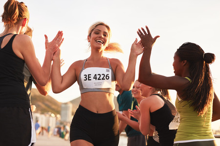 Foto de Multi ethnic group of young adults cheering and high fiving a female athlete crossing finish line. Sportswoman giving high five to her team after finishing the race. - Imagen libre de derechos