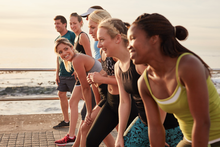 Photo for Group of young athletes in start position, focus on woman. Fit young people preparing for race along sea. - Royalty Free Image