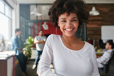 Portrait of smiling young african businesswoman with people in background. Cheerful young woman standing relaxed in her office, looking at camera and smiling.