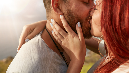 Photo pour Close up shot of loving young couple kissing outdoors. Man and woman kissing each other romantically looking very much in love. - image libre de droit