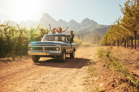 Photo pour Friends having fun in the open back of a vintage truck on a summer day in countryside. Young men and woman enjoying on a road trip. - image libre de droit