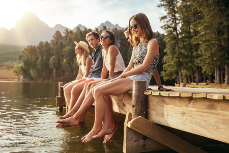 Foto de Portrait of group of young people sitting on the edge of a pier, outdoors in nature. Friends enjoying a day at the lake. - Imagen libre de derechos