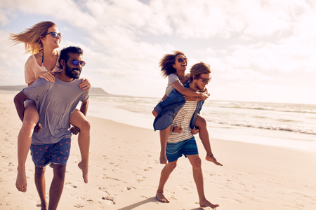 Photo for Two beautiful young couples walking by the beach, with men carrying their women on their back. Couples piggybacking on sea shore. Having fun on beach vacation. - Royalty Free Image