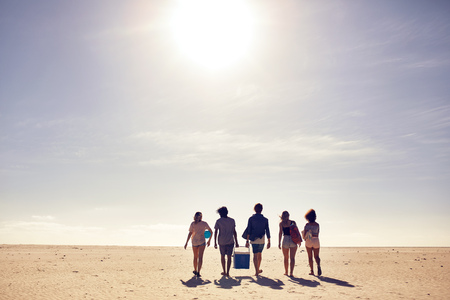 Foto de Rear view portrait of young people carrying cooler box walking on the beach. Looking for a spot for party. Friends on beach vacation, on a hot summer day. - Imagen libre de derechos