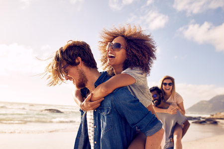Photo pour Group of friends walking along the beach, with men giving piggyback ride to girlfriends. Happy young friends enjoying a day at beach. - image libre de droit