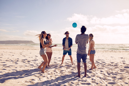 Foto de Group of young people playing with ball at the beach. Young friends enjoying summer holidays on a sandy beach. - Imagen libre de derechos