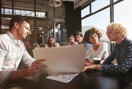 Foto de Happy and successful team of colleagues sitting together to work out business plans - Imagen libre de derechos