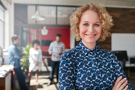 Photo for Portrait of a smiling young female designer standing in her office with some colleagues in the background. - Royalty Free Image