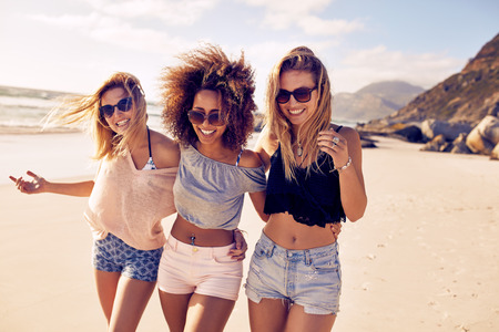 Foto de Portrait of three young female friends walking on the sea shore looking at camera laughing. Multiracial young women strolling along a beach. - Imagen libre de derechos
