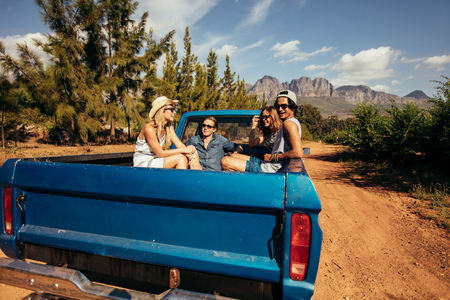 Photo pour Group of friends sitting at the back of a pick up car. Young men and women going on a road trip in nature. - image libre de droit