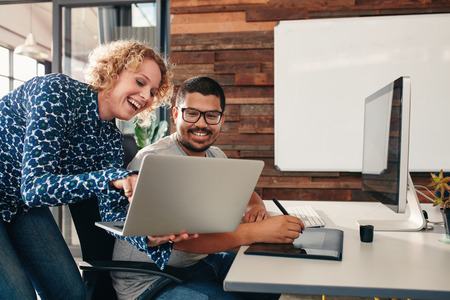 Foto de Shot of two happy young graphic designers working in their office with man sitting at his desk and female colleague showing something on her laptop. - Imagen libre de derechos