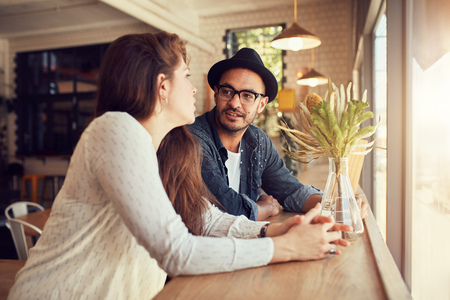 Foto de Portrait of young man and woman sitting at a cafe and talking. Young couple relaxing in a coffee shop. - Imagen libre de derechos