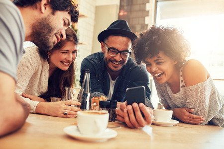 Foto de Portrait of cheerful young friends looking at smart phone while sitting in cafe. Mixed race people sitting at a table in restaurant using mobile phone. - Imagen libre de derechos