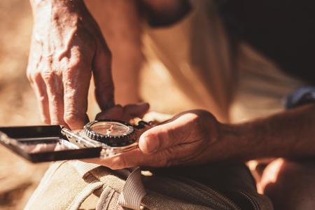 Foto de Close up portrait of man using compass for directions. Focus on compass in hands of a male hiker. - Imagen libre de derechos