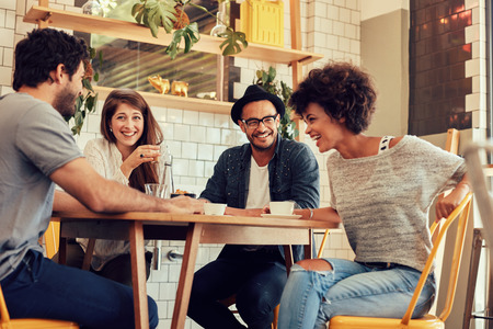 Foto de Portrait of cheerful young friends having fun while talking in a cafe. Group of young people meeting in a cafe. - Imagen libre de derechos