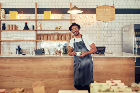 Foto de Portrait of happy young man wearing an apron and hat standing at a cafe counter holding a cup of coffee. Coffee shop owner looking at a camera and smiling. - Imagen libre de derechos