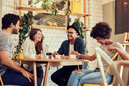 Foto de Group of friends enjoying in cafe together. Young people meeting in a cafe. Young men and women sitting at cafe table and smiling - Imagen libre de derechos