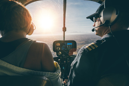 Foto de Rear view of male and female pilots flying a helicopter on sunny day. Man flying a helicopter with his copilot looking outside the aircraft. - Imagen libre de derechos