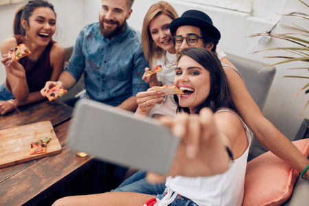 Foto de Group of multiracial young people taking a selfie while eating pizza. Young woman eating pizza her friends sitting around during a party. - Imagen libre de derechos