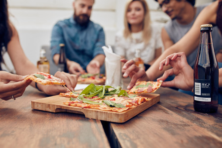 Photo pour Close up shot of pizza on table, with group of young people sitting around and picking up a portion. Friends partying and eating pizza. - image libre de droit