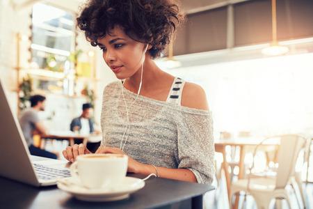 Foto de Portrait of an attractive young woman with earphones using laptop at a cafe. African american woman working on laptop computer at a coffee shop. - Imagen libre de derechos
