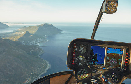 Foto de Aerial view from a helicopter cockpit flying over Cape town. Interior of helicopter cockpit with instruments panel. - Imagen libre de derechos