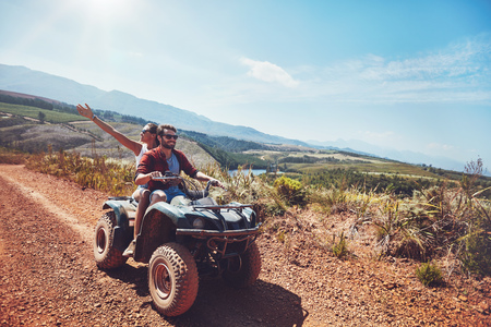 Photo for Young couple on an off road adventure. Man driving quad bike with girlfriend sitting behind and enjoying the ride in nature. - Royalty Free Image