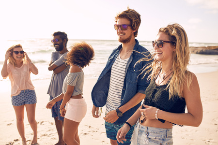 Photo for Group of friends walking along a beach at summertime. Happy young people enjoying a day at beach. - Royalty Free Image