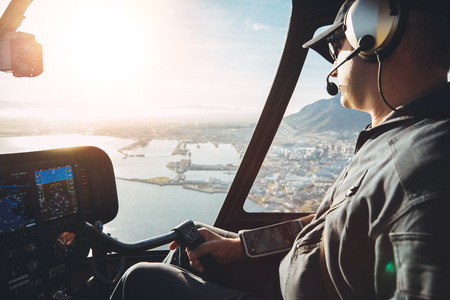 Foto de Male pilot in cockpit of a helicopter flying over cape town city on a bright sunny day. - Imagen libre de derechos