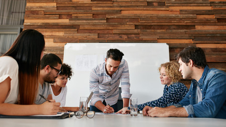 Foto de Group of colleagues having a brainstorming session in conference room. Young man explaining business plans to coworkers during meeting in boardroom. - Imagen libre de derechos