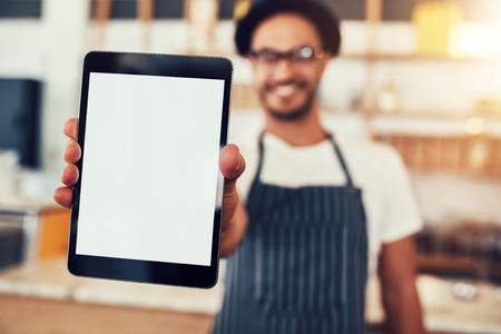 Foto de Close up portrait of a waiter holding up a tablet computer with a empty display. Coffee shop owner showing a digital tablet. - Imagen libre de derechos