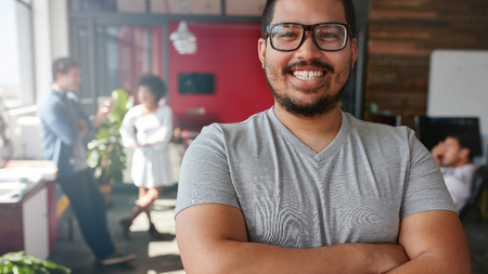 Foto de Smiling male designer looking at camera at office. Mixed race male creative professional with colleagues talking in background. - Imagen libre de derechos