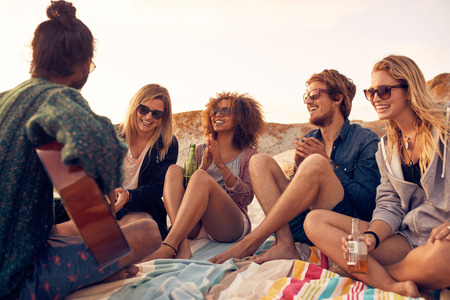 Foto per Group of young people listening to friend playing guitar outdoors. Diverse group of friends hanging out at beach. Young men and women drinking beers and enjoying music. - Immagine Royalty Free