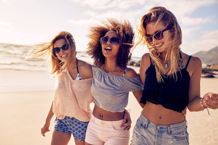 Photo for Group of beautiful young women strolling on a beach. Three friends walking on the beach and laughing on a summer day, enjoying vacation. - Royalty Free Image