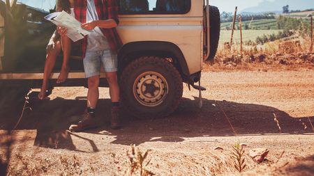 Photo pour Cropped shot of couple with a map on road trip. Young man and woman with car stopping by a country road and reading map for directions. - image libre de droit