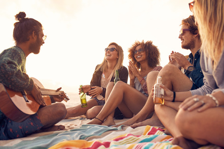 Foto de Happy hipsters relaxing and playing guitar at the beach. Friends drinking beers and listening to music. Having fun at beach party in evening. - Imagen libre de derechos