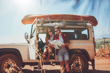 Photo pour Young couple taking a break to look at a map while on a roadtrip. Young man and woman on country road looking for directions on map. - image libre de droit