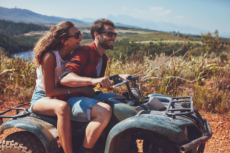 Foto de Man and woman having fun on an off road adventure. Couple riding on a quad bike in countryside on a summer day. - Imagen libre de derechos
