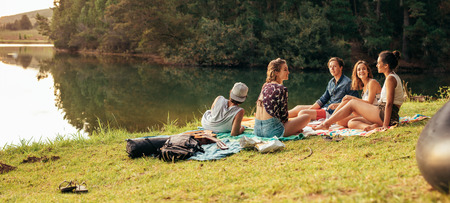 Photo for Young friends having picnic near a lake. Young friends enjoying a day at the lake. - Royalty Free Image