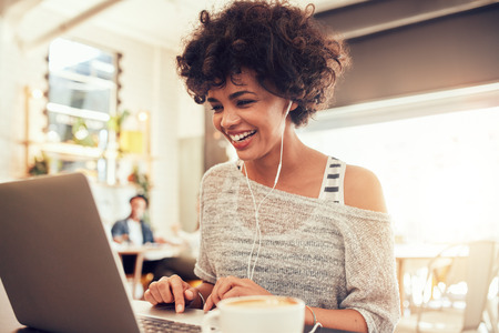 Foto de Image of happy woman using laptop while sitting at cafe. Young african american woman sitting in a coffee shop and working on laptop. - Imagen libre de derechos