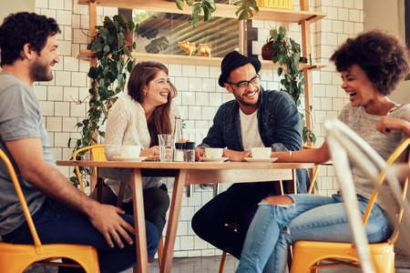 Foto de Young people having a great time in cafe. Friends smiling and sitting in a coffee shop, drinking coffee and enjoying together. - Imagen libre de derechos