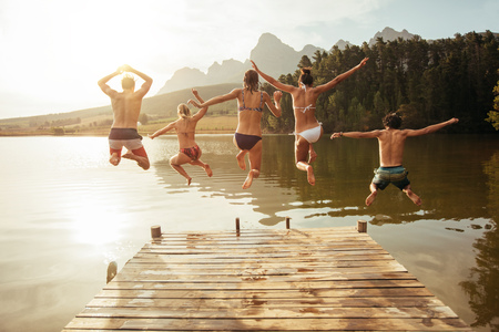 Photo for Portrait of young friends jumping from jetty into lake. Friends in mid air on a sunny day at the lake. - Royalty Free Image