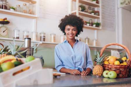 Photo pour Portrait of beautiful young woman standing at counter in juice bar smiling to camera. African female juice bar owner. - image libre de droit