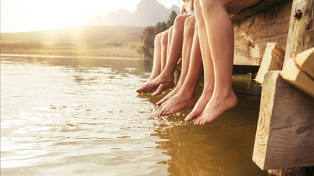 Photo for Four young friends sitting on jetting with their legs hanging down to the water on a summer day. Focus on legs of young people. - Royalty Free Image