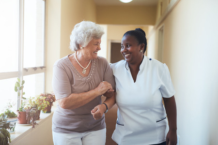 Photo pour Portrait of smiling home caregiver and senior woman walking together through a corridor. Healthcare worker taking care of elderly woman. - image libre de droit