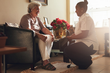 Foto de Senior woman sitting on a chair at home with female caregiver holding blood pressure gauge.  Female nurse visiting senior patient for checking blood pressure. - Imagen libre de derechos