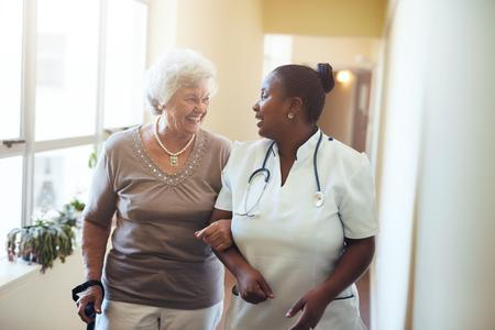 Foto de Senior woman walking in the nursing home supported by a caregiver. Nurse assisting senior woman. - Imagen libre de derechos