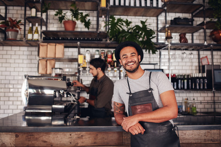 Photo for Coffee shop worker smiling to camera, standing at the counter. Happy young man in apron and hat leaning to cafe counter, with waiter working in background. - Royalty Free Image